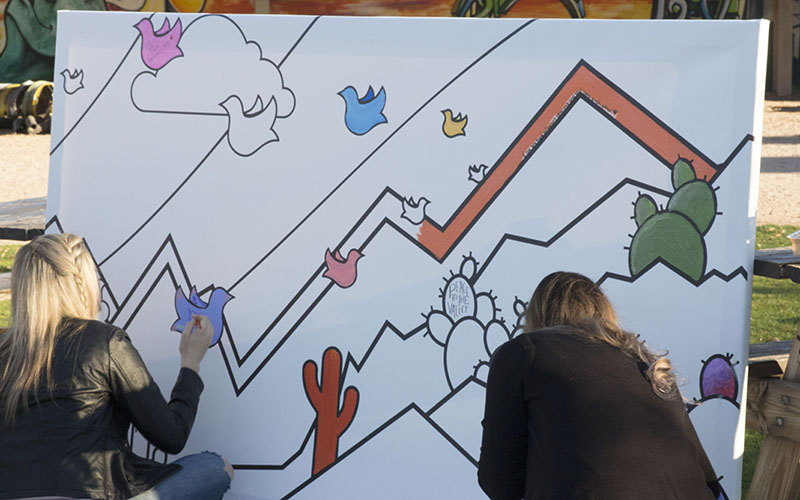 Women added colorful touches to the mural in the Roosevelt Row Pop-Up Park, before it is moved to the New City Studio. (Photo by Rachael Bouley/Cronkite News)