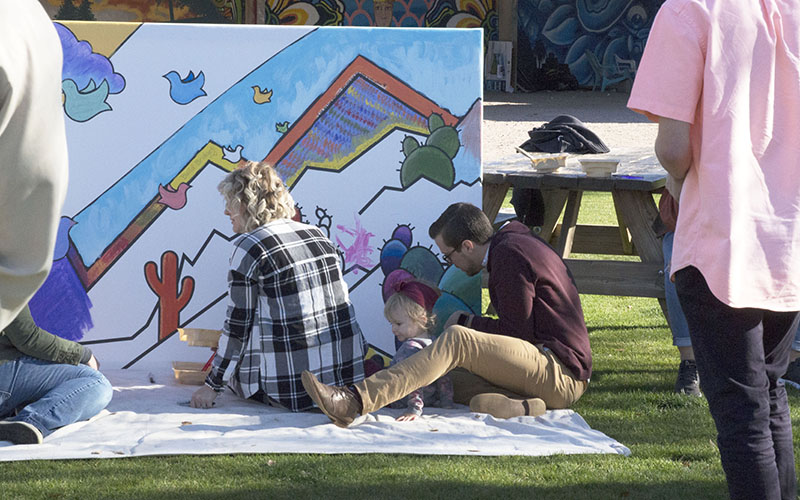 It was a family affair for Jason Ake, the creavtive director at Central Christian Church, who was joined by his wife and young daughter as they all contributed to the mural. (Photo by Rachael Bouley/Cronkite News)