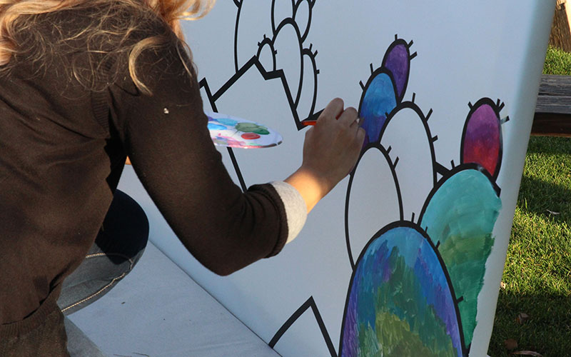 Each painter did their part to complete a small section of the mural which will be unveiled at New City Studio. (Photo by Rachael Bouley/Cronkite News)