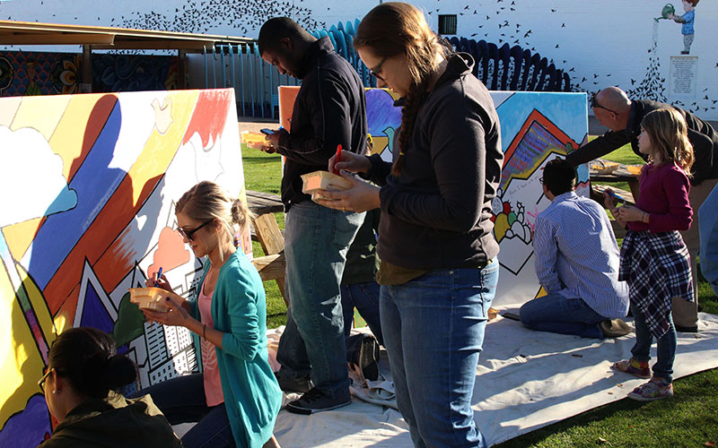 The blank canvas was transformed into a colorful mural as people took turns adding their messaes of peace. (Photo by Rachael Bouley/Cronkite News)
