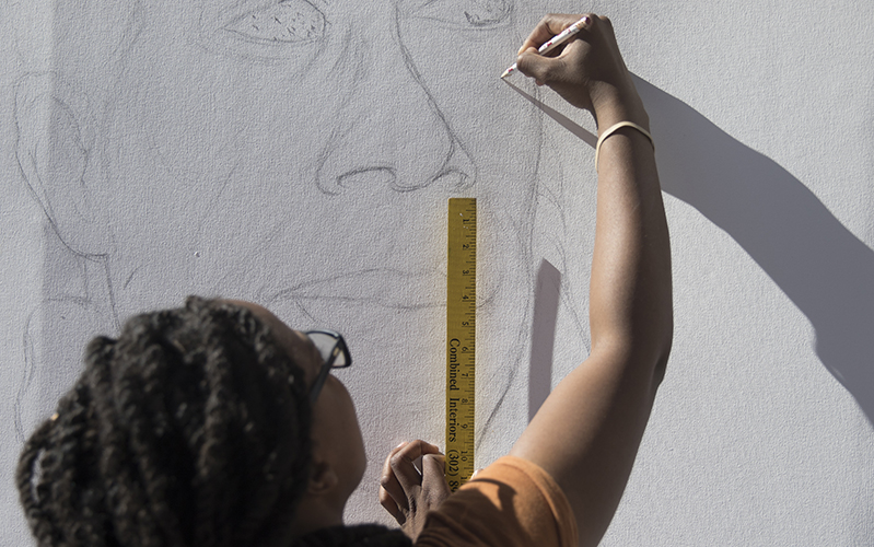 Lead artist Kyra Trent begins sketching out the details of James Baldwin's portrait. (Photo by Josh Orcutt/Cronkite News)