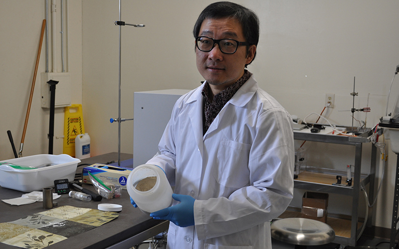 Jinhong Zhang, a professor at the University of Arizona, has spent three years working with fly ash, a waste product from coal-burning power plants. (Photo by Courtney Kock/Cronkite News)