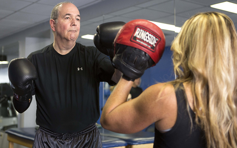 Steve Shenkman trains with Nicole Greene at Edge Fitness in Scottsdale. Shenkman has been doing boxing for more than a year to help minimize the symptoms of Parkinson's disease. (Photo by Johanna Huckeba/Cronkite News)