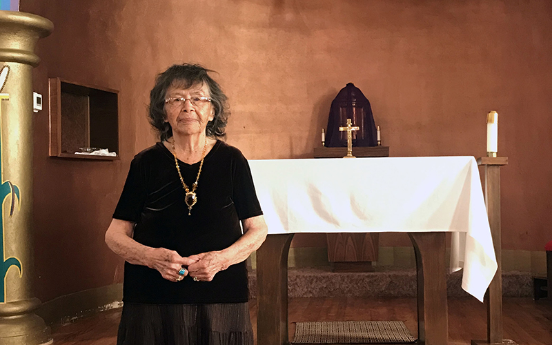 Nellie Shirley stands inside the church building where she has practiced her Catholic faith nearly all of her life.