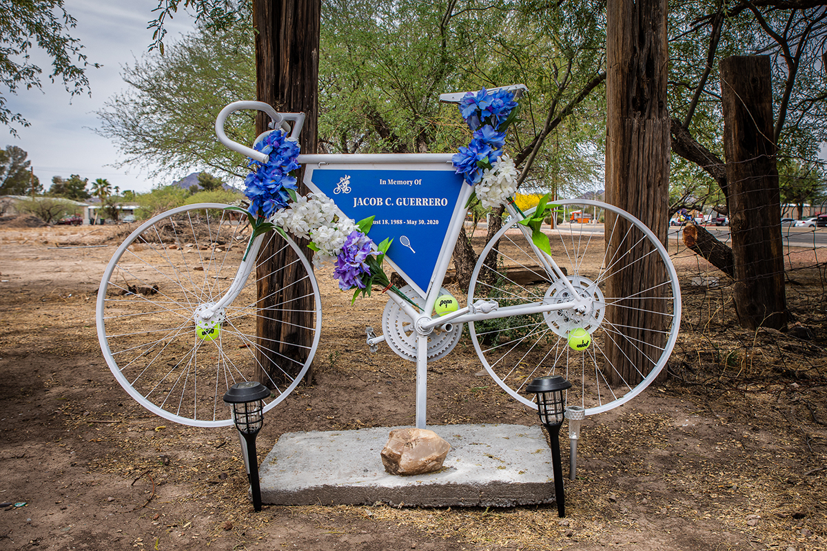 A ghost bike sits at the site of Jacob Guerrero's overdose death in Tucson. Theresa Guerrero, his mother, placed the commemorative bicycle adorned with tennis balls, symbolizing two of his favorite pastimes, to remember her son's spirit. (Photo by Alberto Mariani/Cronkite News)