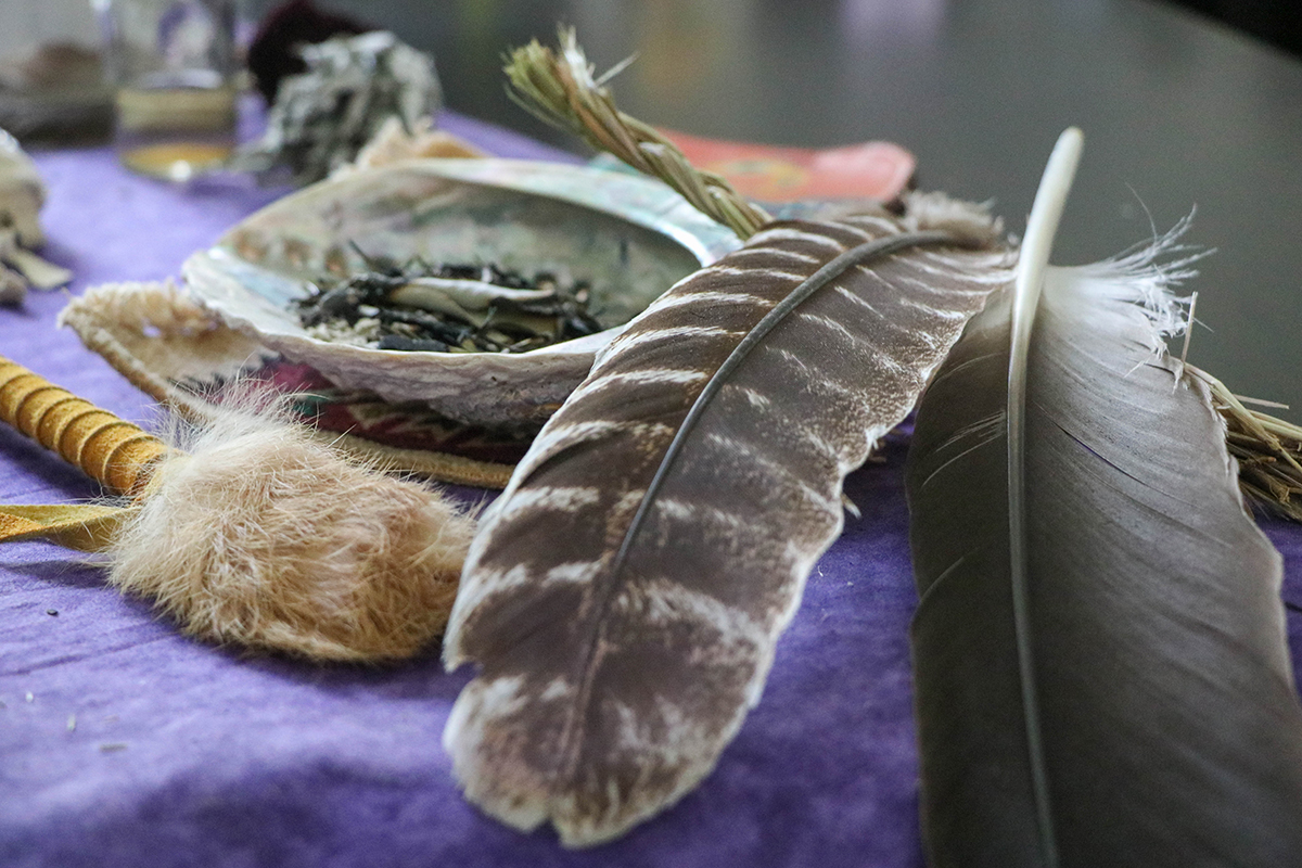 Eagle feathers and dried sage in a seashell are among the sacred items that Andrea Klimas, clinical director at Native American Connections, brings to talking circles. Incorporating such Indigenous practices into health care treatment isn't new but has grown in significance during the pandemic, which has disproportionately affected Native communities. (Photo by Gianluca D'Elia/Cronkite News)