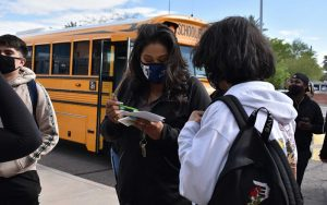 A masked school official talks with a student